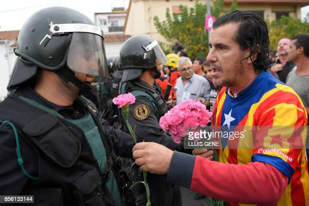 TOPSHOT A man gives a carnation to a Spanish Guardia Civil guard in Sant Julia de Ramis on October 1 on the day of a referendum on independence for...