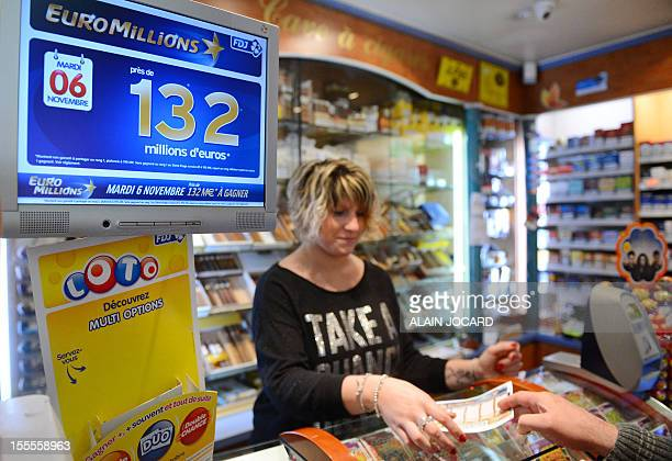 A man gives a vendor a filled Euro Millions lottery ticket on November 5 2012 in Tours central France Gamblers across Europe are to go neckandneck...