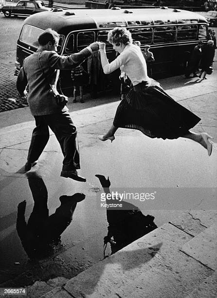 A man gives a woman a helping hand as she takes a flying leap over a large puddle on the pavement