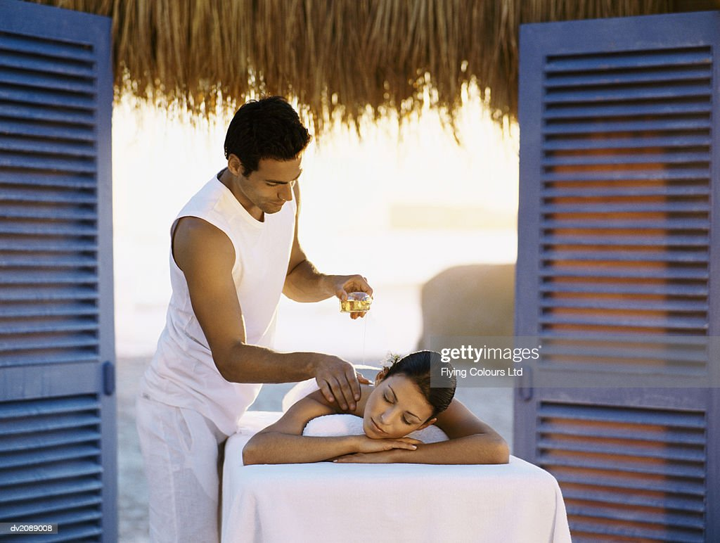 Man Gives a Woman a Massage With Oils : Stock Photo
