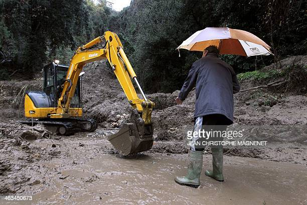 A man gives directions to an excavator clearing a blocked road following a landslide in Menton southeastern France on January 18 2014 Many roads have...