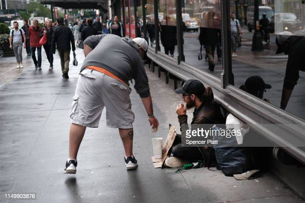 A man gives money to a person claiming to be homeless on a Manhattan sidewalk on May 17 2019 in New York City As New York City Mayor Bill de Blasio...