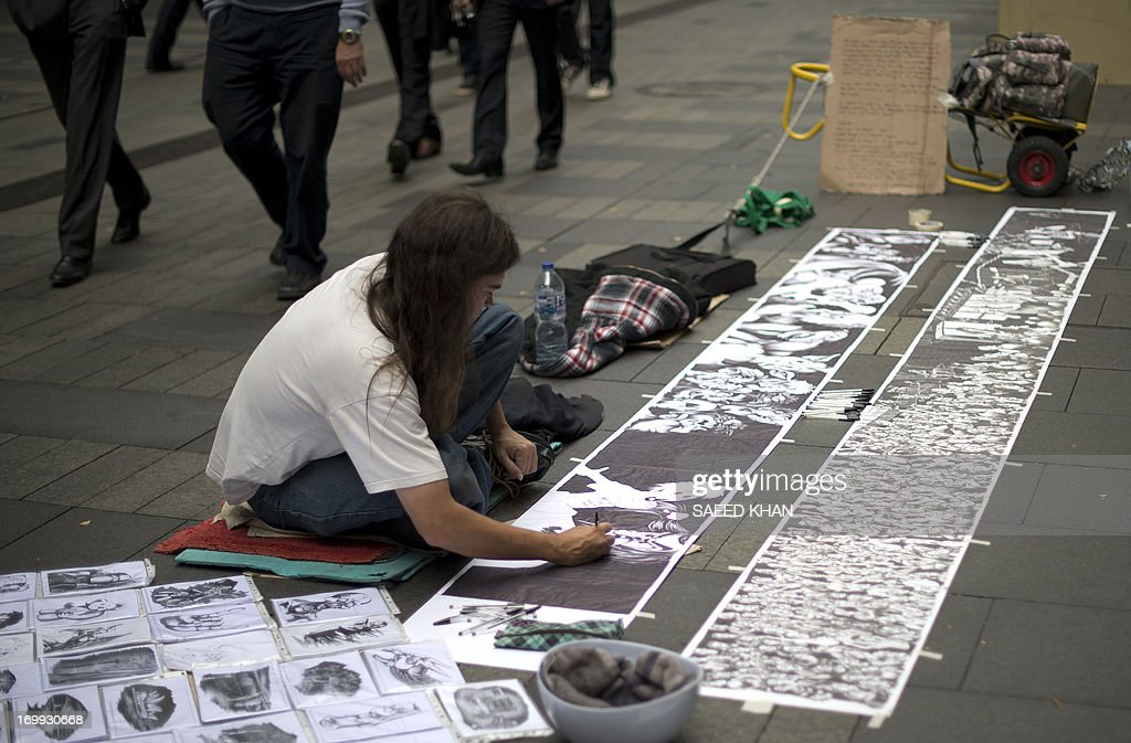 A man gives the finishing touches to his art work in the central business district of Sydney on June 5, 2013. Homelessness in Australia has surged 17 percent since 2006 mainly due to a spike in migrant numbers, though fewer people are sleeping rough on the streets, a report found. The National Affordable Housing Agreement report, prepared by the government's COAG Reform Council, found that overall housing security had declined from 2006 to 2011. AFP PHOTO / Saeed KHAN