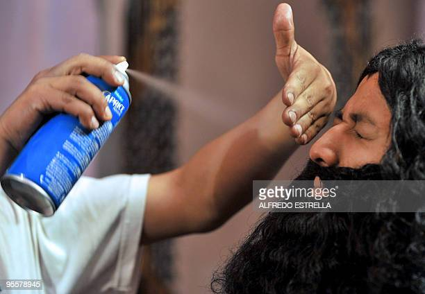 A man gives the finishing touches to the false beard of 'Gaspar' during the preparation of the Three Wise Men in Mexico City's Guerrero neighbourhood...