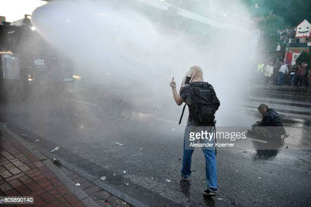 """Man gives the one finger gesture to police as he is drenched in water from water cannons during the """"Welcome to Hell"""" protest march on July 6, 2017..."""