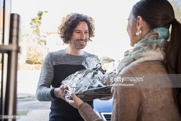 Man giving a gift to his friend at front door, Munich, Bavaria, Germany
