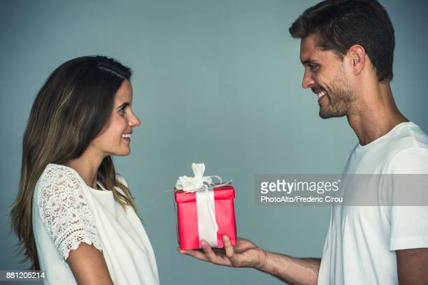 man giving a gift to his girlfriend - geben stock-fotos und bilder