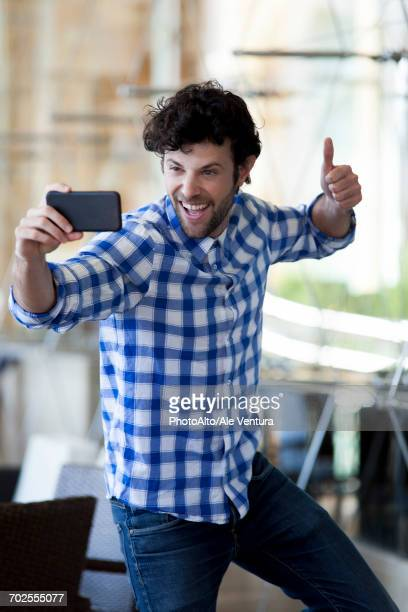 Man giving a thumbs up whiile taking a selfie with his smartphone