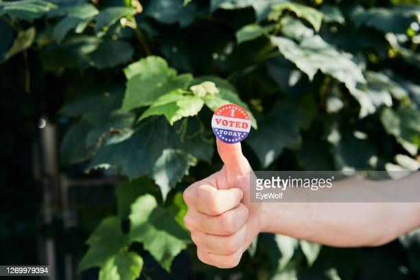 """a man giving a thumbs up with a """"i voted today"""" sticker on his thumb. - sticker stock pictures, royalty-free photos & images"""