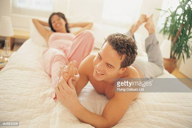 man giving a woman a foot massage in bed - woman lying on stomach with feet up stock photos and pictures