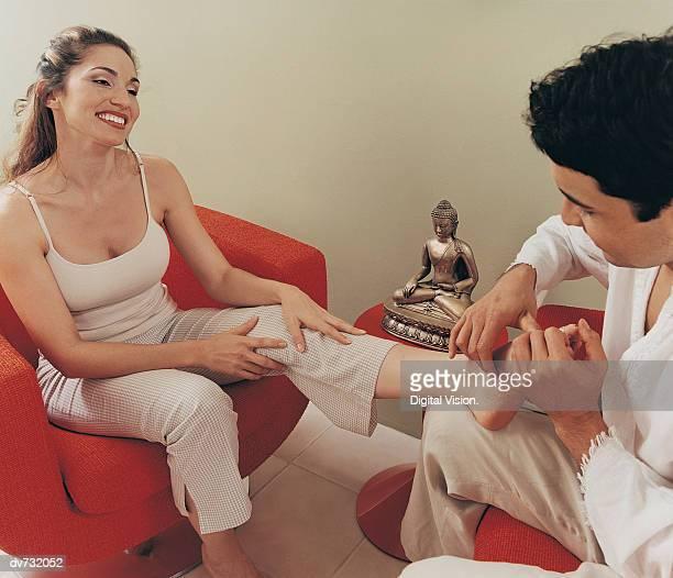 Man Giving a Woman a Foot Massage