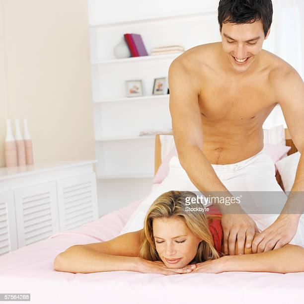 Man giving a woman a massage in bed