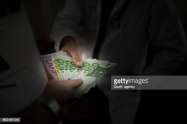 man giving bribe to a doctor - corruption stock pictures, royalty-free photos & images
