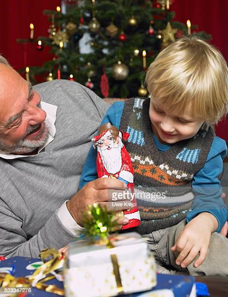 Man Giving Chocolate Santa to Grandson