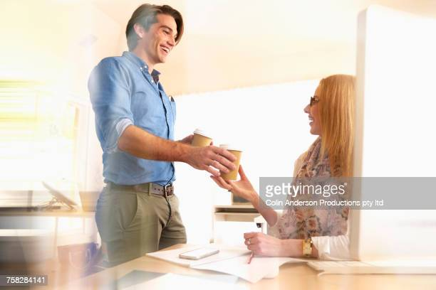 Man giving coffee to woman in office