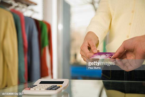Man giving credit card to sales clerk in store, close-up, mid section