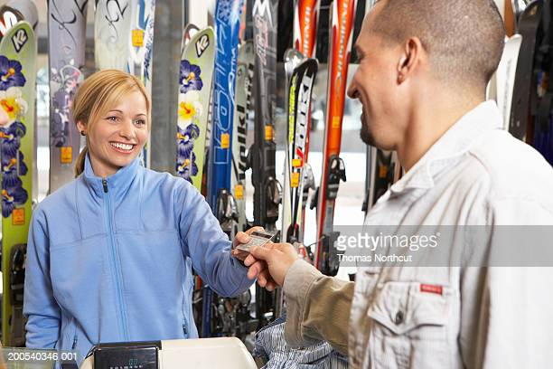 Man giving credit card to salesclerk in sports shop