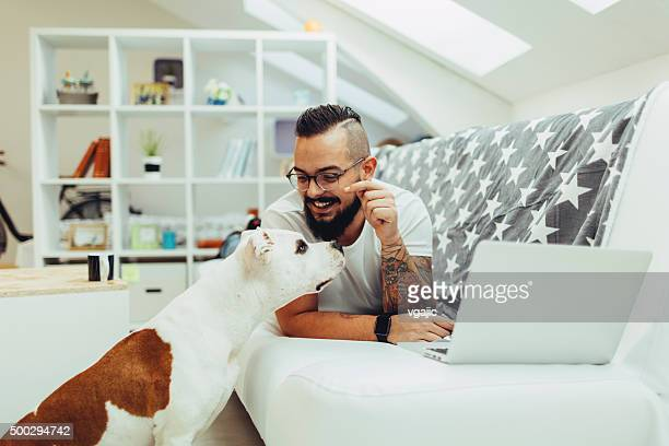 Man giving dog biscuit to his pet at home.