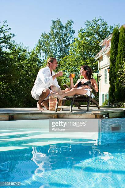Man giving drink to woman sitting near swimming pool