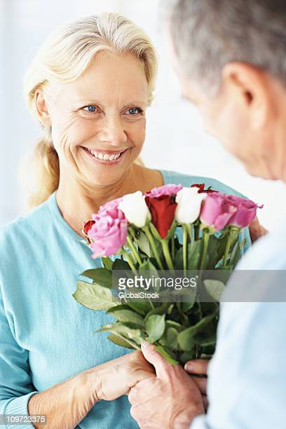 Man giving flowers to a woman on their anniversary