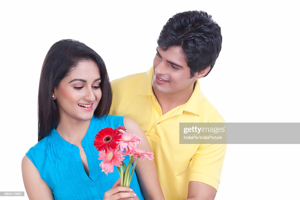 Man giving flowers to his girl friend : Stock Photo