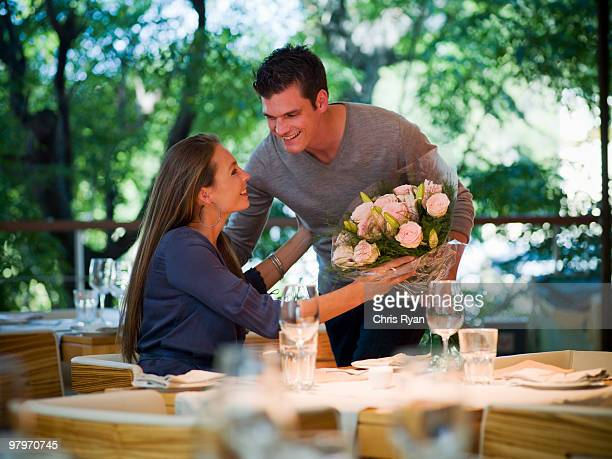 Man giving flowers to woman at restaurant table