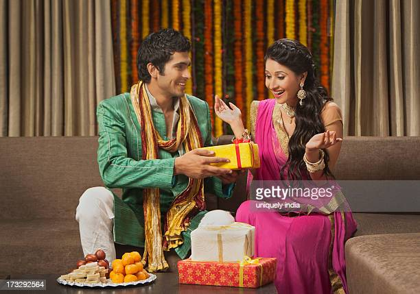 man giving gift to his girlfriend on diwali - diwali sweets stock photos and pictures