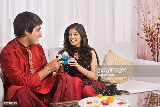 Man giving gift to his sister at Raksha Bandhan