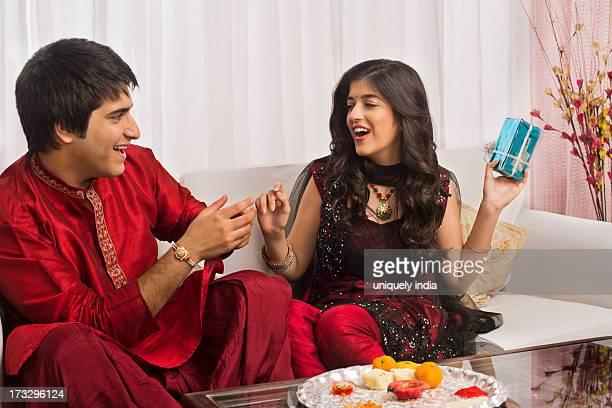 man giving gift to his sister at raksha bandhan - raksha bandhan stock photos and pictures
