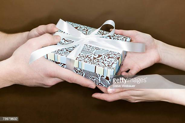 Man giving gift to woman, close-up of hands