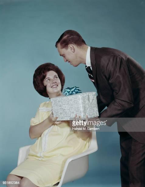 man giving gift to woman, smiling - heterosexuelles paar stock-fotos und bilder