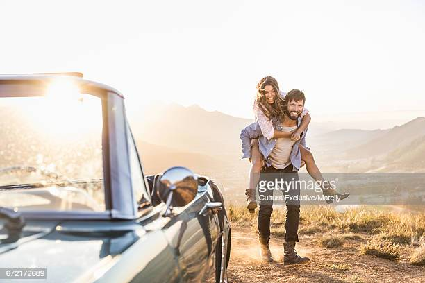 Man giving girlfriend a piggy back by vintage convertible at sunset, Franchook, South Africa