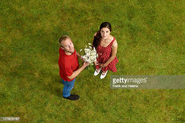 Man giving girlfriend flowers outdoors