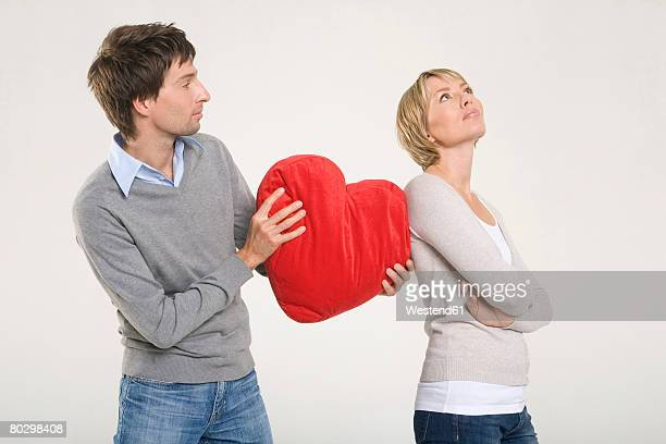 Man giving heart-shaped cushion to woman
