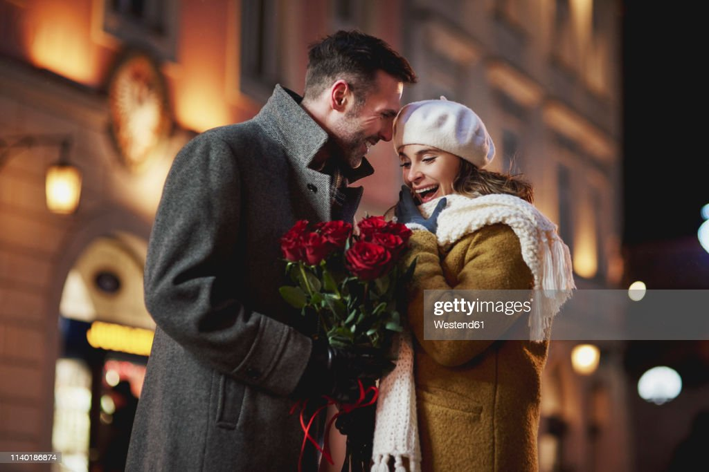 Man giving his amazed girlfriend bunch of red roses on Valentine's Day : Stock Photo