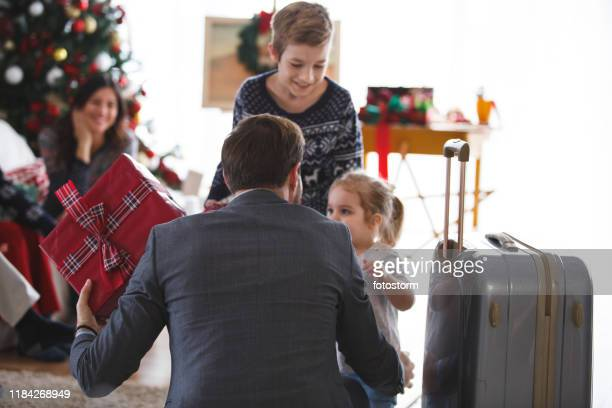 man giving his children presents after he got back from business trip - hello december stock pictures, royalty-free photos & images