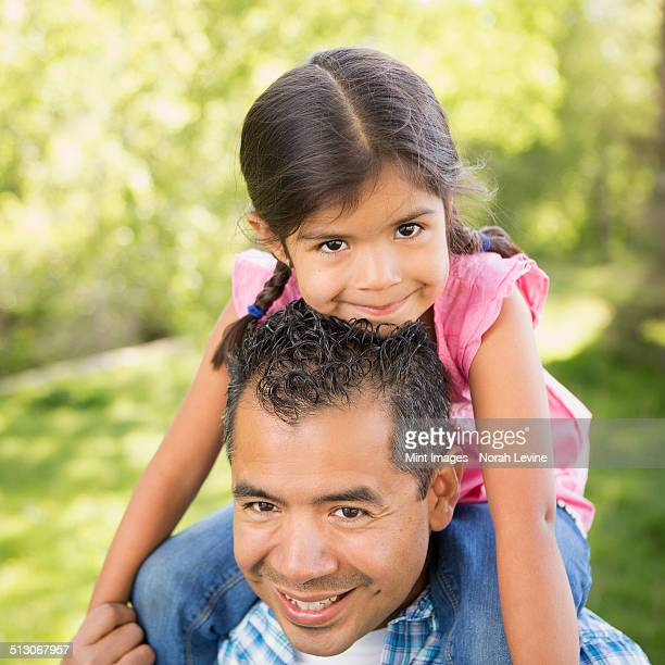 A man giving his daughter a piggyback ride on his shoulders.