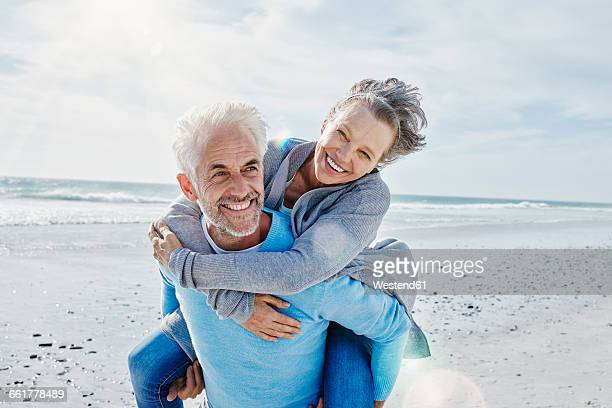 man giving his wife a piggyback ride on the beach - 50 59 years stock pictures, royalty-free photos & images