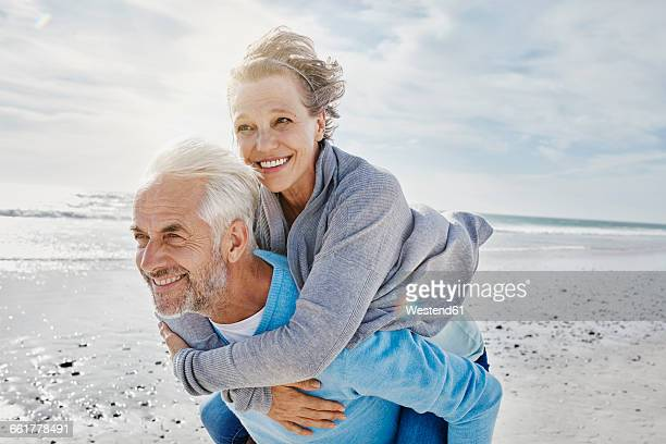 Man giving his wife a piggyback ride on the beach