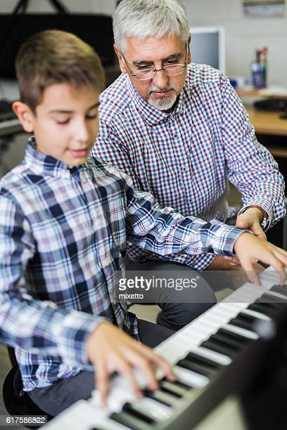 man giving lesson piano to boy - musical equipment stock pictures, royalty-free photos & images