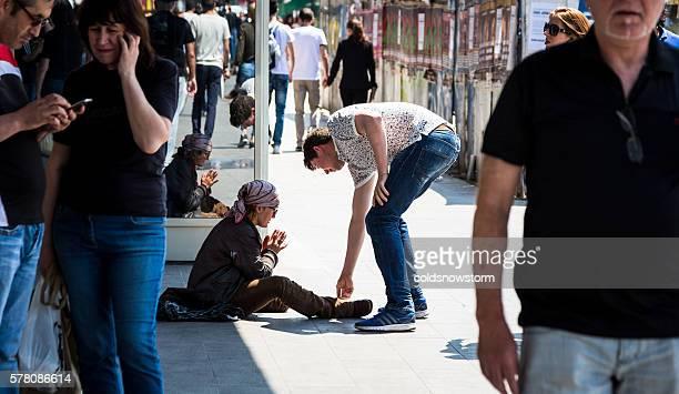Man giving money to homeless street woman in Bucharest, Romania