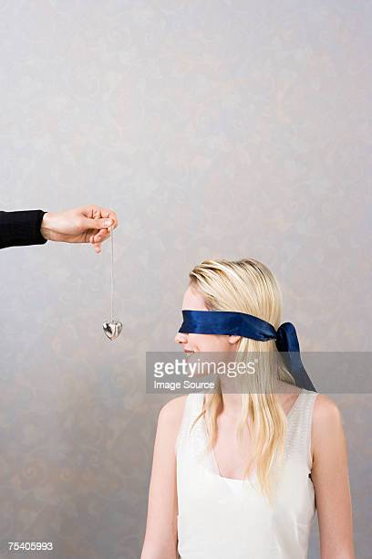 Man giving necklace to blindfolded woman