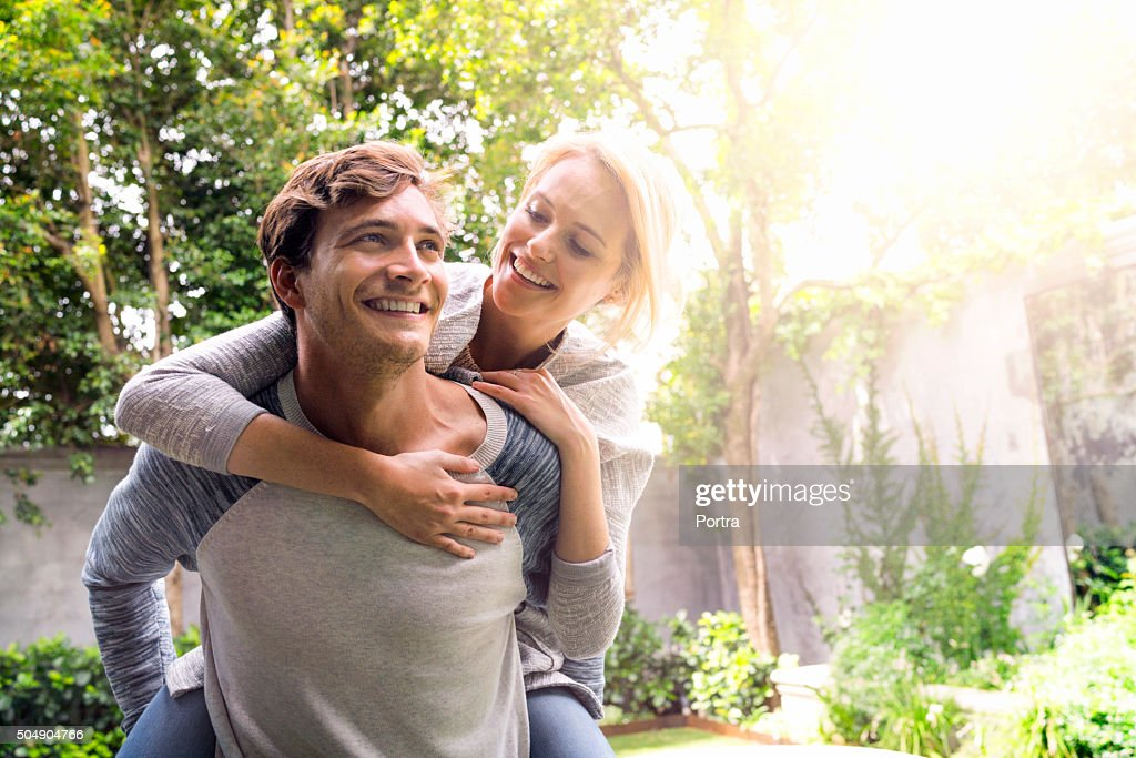Man giving piggyback ride to woman in backyard : Stock Photo