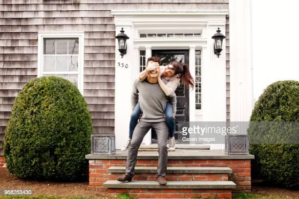 man giving piggyback to woman while standing on front stoop - augen zuhalten stock-fotos und bilder