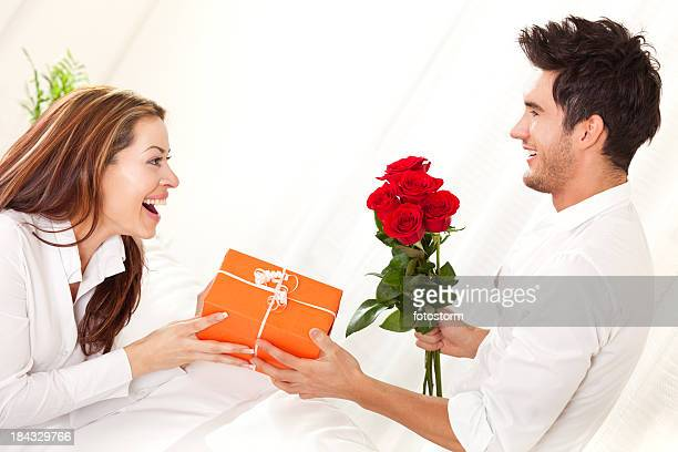 Man giving present and bouquet of red roses to woman