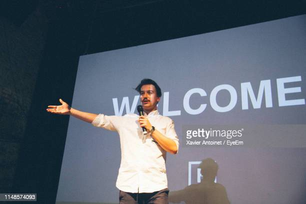 man giving presentation while standing in front of projection screen - präsentation rede stock-fotos und bilder