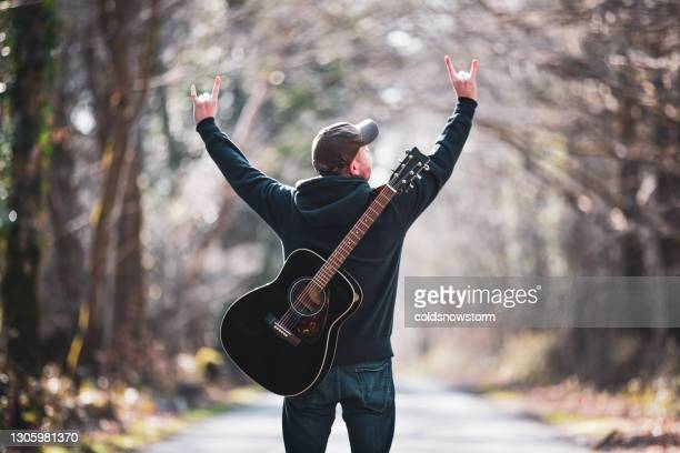 man giving sign of the horns hand gesture on open road with guitar on back - rock music stock pictures, royalty-free photos & images