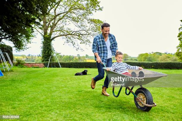 man giving son ride in wheelbarrow - wheelbarrow stock photos and pictures