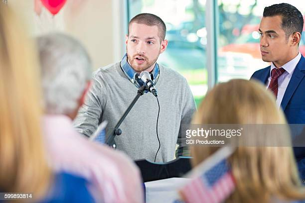 man giving speech at podium during town hall meeting - town hall meeting stock photos and pictures