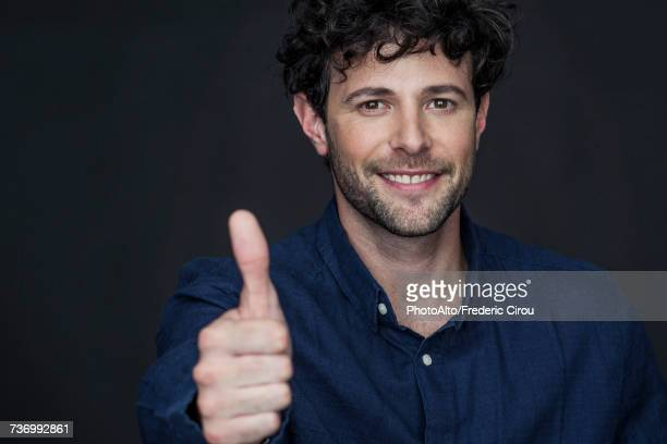 Man giving thumbs up and smiling, portrait